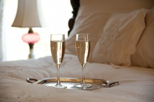 two glasses of champagne on bed with down comforter