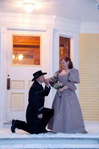 bridegroom kneels before his bride in 1800's period costume after their wedding at the Governor's House