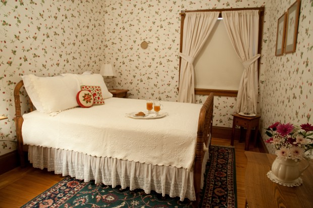 double bed with lace bed skirt in room with strawberry wallpaper