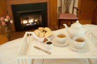 bedtray with tea and scones and fireplace in he background