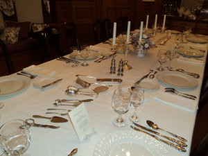 Place settings in different stsyles and display of silver serving pieces
