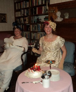 two ladies in period costume seated with a birthday cake decorated with fruit