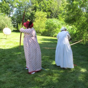 two ladies in Regency gowns practice their archery at the Jane Austen weekend