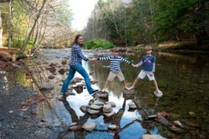mom and two boys on the rocks in the river