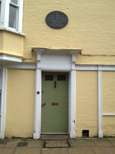 yelloe house with plaque: Jane Austen died here