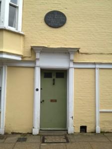 yelloe house with plaque: Jane Austen died here