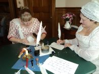 Two ladies in Regency dress are writing with quilll pens.